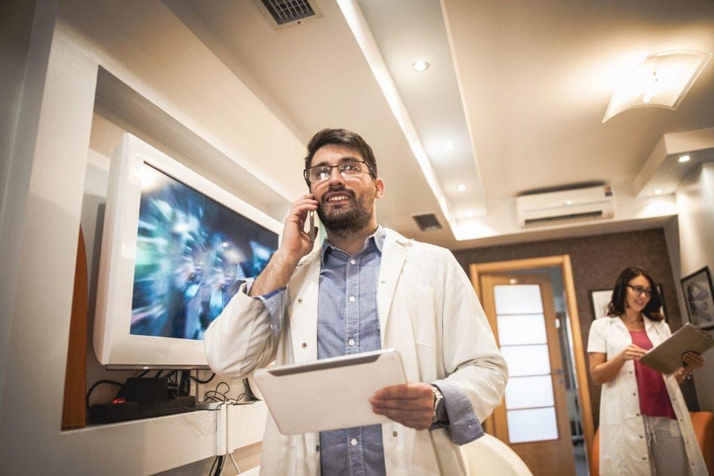 Un doctor camina por una clínica hablando por teléfono y llevando una Tablet en la mano. Sonríe y se le ve satisfecho, está realizando una llamada de seguimiento a un paciente dentro de las acciones de captación orgánica de pacientes de Medicalta, marketing sanitario para clínicas y clínicas dentales.
