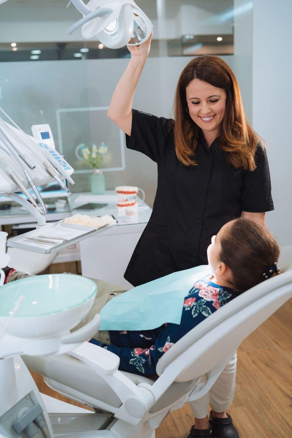 Dentista examinando los dientes de una niña mientras le sonríe y le acerca la lámpara en una clínica de dental diseñada por Medicalta, marketing sanitario para clínicas.