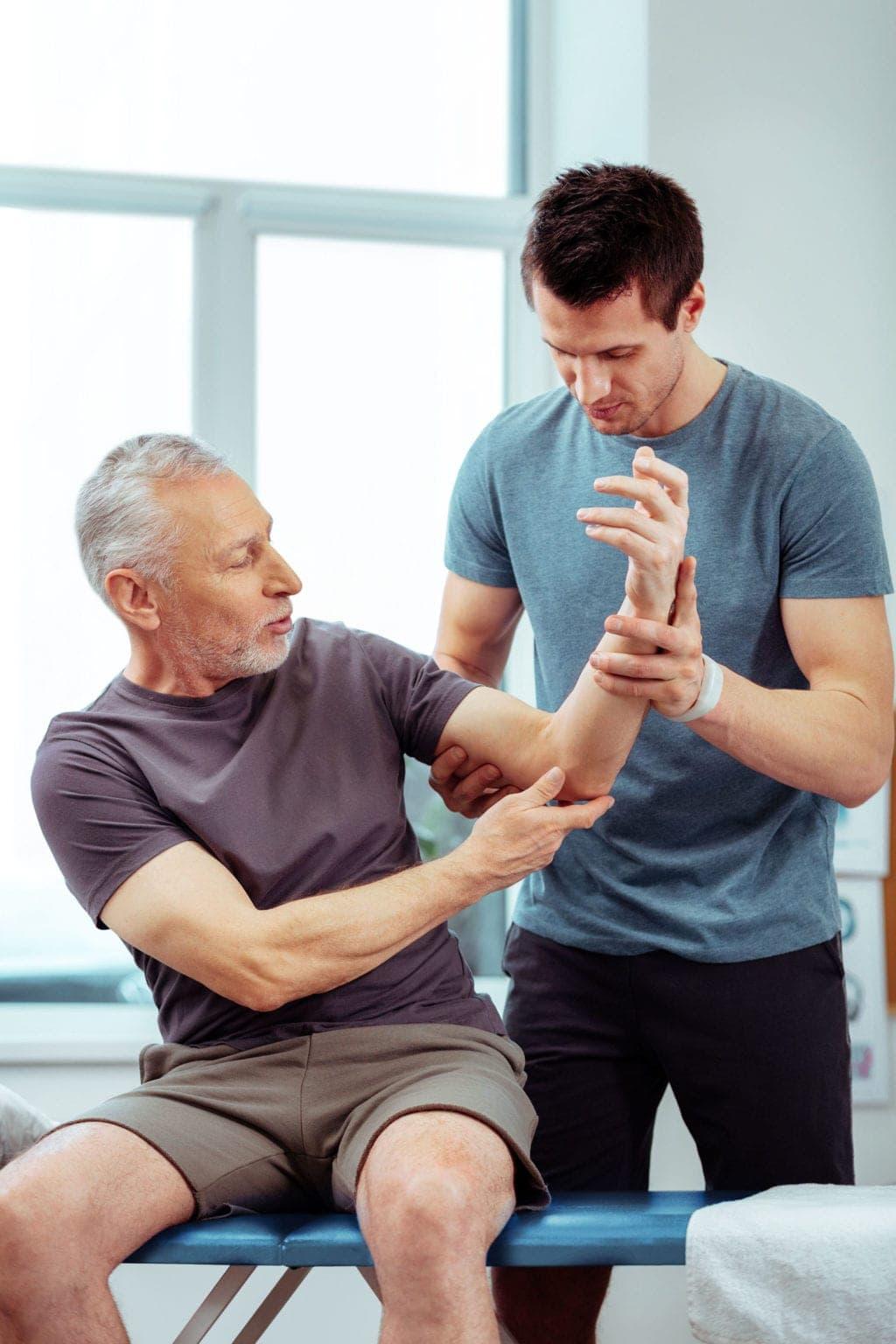 Fisioterapeuta revisa la movilidad del brazo de un hombre anciano que sostiene su mano izquierda hacia arriba en una clínica de fisioterapia diseñada por Medicalta, marketing sanitario para clínicas.