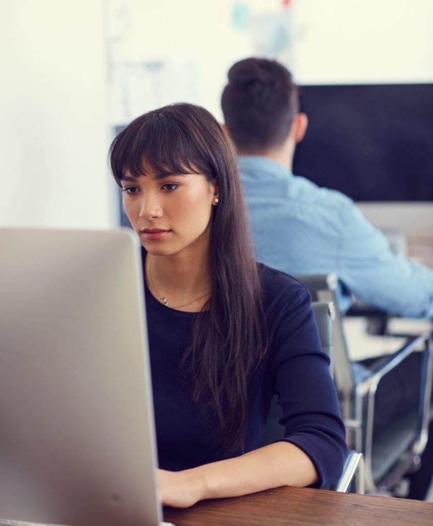 Una desarrolladora joven en la oficina de Medicalta trabaja en su ordenador de sobremesa en labores de Construcción de marca para una clínica dental cliente de Medicalta - marketing sanitario para clínicas y clínicas dentales.