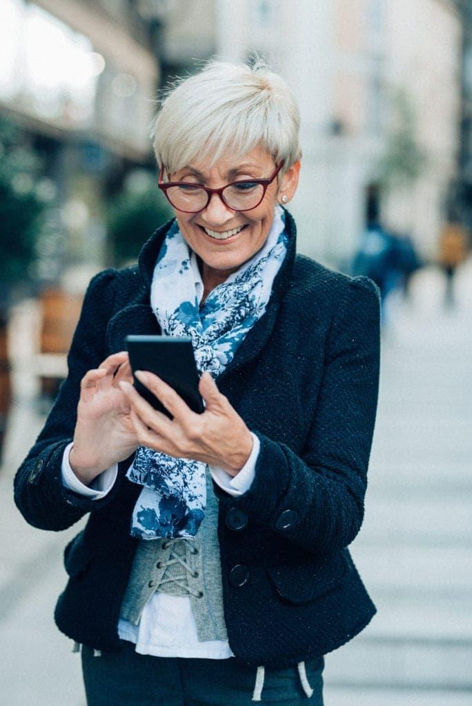 Mujer madura sonríe con satisfacción mientras caminando por la calle ve en su teléfono móvil una página web de una clínica dental, los dentistas confiaron el desarrollo de la web en Medicalta - marketing sanitario para clínicas y han conseguido aumentar el tráfico un 200% y la conversión un 450%