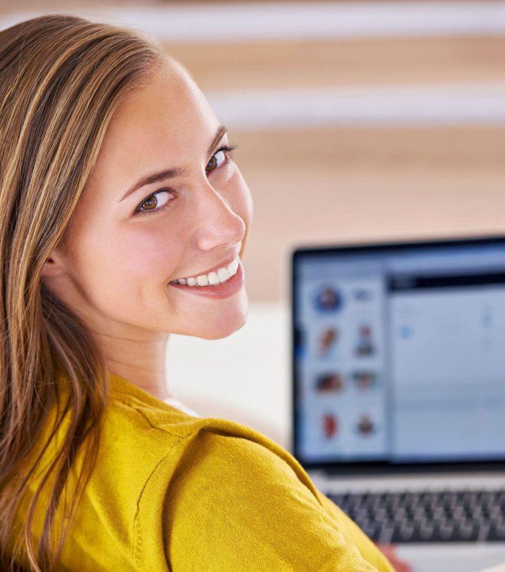Una chica de espalda con jersey amarillo mira a cámara girando la cabeza hacia la misma mientras está con un ordenador portátil en las rodillas se ve que acaba de entrar en una página de una clínica dental gracias una campaña de publicidad sanitaria digital realizada por Medicalta, marketing sanitario para clínicas.