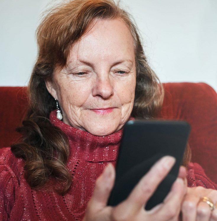 Sonriendo, una mujer mayor usa el móvil con absoluta confianza. Está mirando la web de una clínica en la que va a reservar una cita tras hacerle sido recomendada por una amiga, la clínica había activado un plan de Captación orgánica de Pacientes con Medicalta, marketing sanitario para clínicas y clínicas dentales.