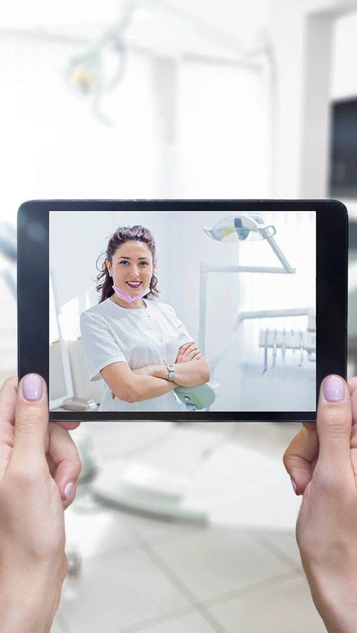 Horizontal color image of female hands holding digital tablet, dentist's chair and dental equipment.