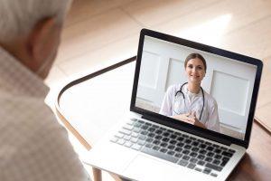 Un hombre mayor está consultando a través de una videoconferencia su estado de salud con una doctora, el hombre, de espaldas, mira la pantalla de un ordenador portátil donde una doctora sonriente escucha con atención la consulta en un proceso de Fidelización de Pacientes creado por Medicalta - marketing sanitario para clínicas y clínicas dentales.