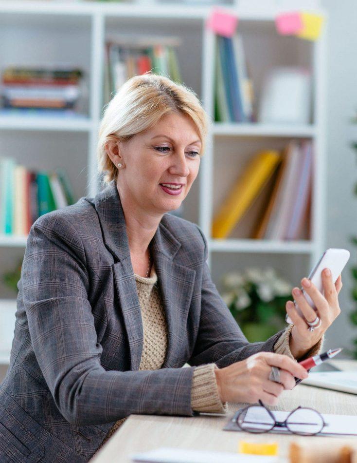 Una mujer de mediana edad sonríe en una reunión de grupo al mismo tiempo que charla con sus compañeros la escena representa un estudio de trabajo de investigación de mercado creado por Medicalta - marketing sanitario para clínicas.