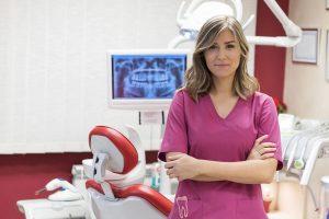 Una dentista joven mira a cámara y esboza una media sonrisa es una persona conocida que tiene una buena reputación profesional y ha contratado un plan de marketing digital Medicalta, marketing sanitario para clínicas y clínicas dentales.
