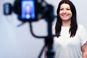 Mujer sonriente mira a cámara viste una camiseta blanca y su pelo está desaliñado, se la observa contenta y está frente a una cámara porque va a grabar un testimonial para una clínica de fisioterapia dentro de una campaña de Vídeo-Testimonios de Pacientes de Medicalta, marketing sanitario para clínicas y clínicas de fisioterapia.