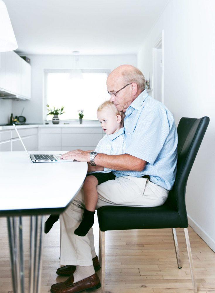 Un abuelo y su nieto miran un ordenador disfrutando de unos buenos momentos en familia viendo el blog de una clínica que ha contratado su Web, móvil y contenidos digitales a Medicalta, marketing sanitario para clínicas y clínicas dentales.