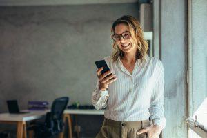 Sonriendo, una mujer joven en una oficina usa el móvil con absoluta confianza. Está mirando la web de una clínica creada con un plan de Web, móvil y contenidos digitales de Medicalta, marketing sanitario para clínicas y clínicas dentales.